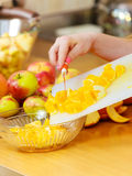 Woman housewife in kitchen cutting orange fruits Stock Photo