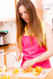 Woman housewife in kitchen cutting orange fruits Royalty Free Stock Image
