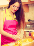 Woman housewife in kitchen cutting orange fruits Royalty Free Stock Photo