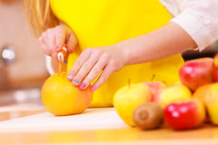 Woman housewife in kitchen cutting orange fruits Stock Photos