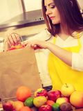 Woman housewife in kitchen with many fruits Stock Photos