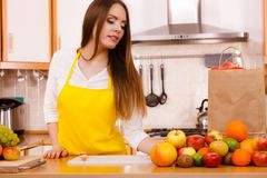 Woman housewife in kitchen with many fruits royalty free stock photography