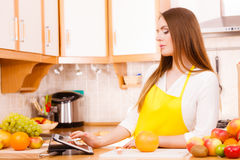 Woman housewife in kitchen using tablet Stock Photography