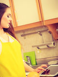 Woman housewife in kitchen using tablet Stock Images