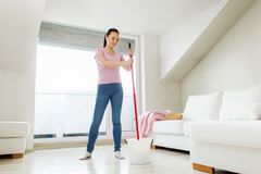 Woman or housewife with mop cleaning floor at home. People, housework and housekeeping concept - happy woman or housewife with mop cleaning floor and dancing at Stock Images