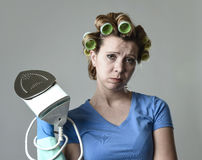 Woman or housewife sad bored and stressed holding iron angry and frustrated. Young attractive woman or housewife sad bored and stressed holding iron angry and royalty free stock photo