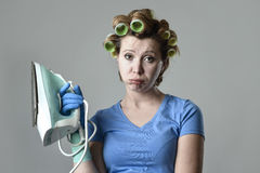 Woman or housewife sad bored and stressed holding iron angry and frustrated. Young attractive woman or housewife sad bored and stressed holding iron angry and stock photos
