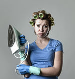 Woman or housewife sad bored and stressed holding iron angry and frustrated. Young attractive woman or housewife sad bored and stressed holding iron angry and royalty free stock images