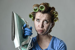 Woman or housewife sad bored and stressed holding iron angry and frustrated. Young attractive woman or housewife sad bored and stressed holding iron angry and stock photography