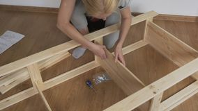 Woman housewife sitting in the room on the floor, collects wooden rack, bought in the store. Assembly of furniture. stock footage