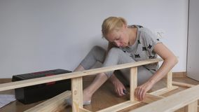 Woman housewife sitting in the room on the floor, collects wooden rack, bought in the store. Assembly of furniture. stock video footage