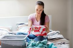 Woman or housewife sorting laundry at home. Household and people concept - woman or housewife sorting laundry at home Royalty Free Stock Photo