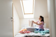 Woman or housewife sorting laundry at home. Household and people concept - woman or housewife sorting laundry at home Royalty Free Stock Images