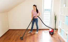 Woman or housewife with vacuum cleaner at home. Household, housework and cleaning concept - happy woman or housewife with vacuum cleaner at home Stock Photos