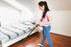 Woman or housewife with vacuum cleaner at home. Household, housework and cleaning concept - happy woman or housewife with vacuum cleaner at home Royalty Free Stock Photos