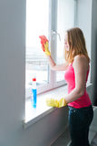 Woman housewife washes a window Royalty Free Stock Photography