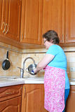 Woman housewife washing dishes in the kitchen Royalty Free Stock Image