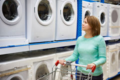 Woman housewife whit shopping cart shopping for washing machine Royalty Free Stock Images
