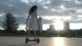 Woman on hoverboard in back lit stock video