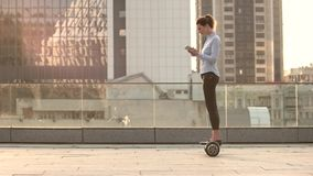 Woman on hoverboard, urban background. Businesswoman with tablet. World of possibilities stock video