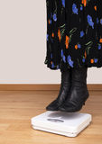 Woman hovers, floats above scales - lose weight, weightloss conc Royalty Free Stock Images
