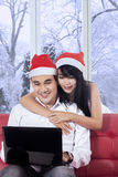 Woman hug her boyfriend while using laptop Stock Image