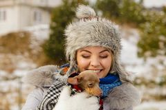 Woman hug warming her little dog in winter stock image