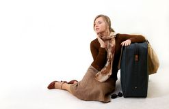 Woman with huge bag. Beauty woman with huge bag is siting on station, separate on white Royalty Free Stock Photos