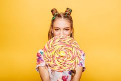 Woman with huge candy instead of a head. Beautiful young woman with huge candy instead of a head. Big colorful caramel lollypop in hands of woman. Portrait of Royalty Free Stock Photography