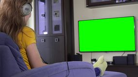 Woman with huge headphones have fun watching tv. Green chroma key screen stock video
