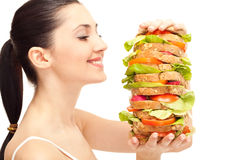 Woman with huge healthy sandwich. Pretty woman with huge healthy sandwich, smiling, isolated on white Royalty Free Stock Images