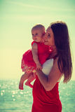 Woman hugging baby on beach near water Stock Image