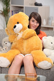 Woman hugging big teddy bear Stock Images