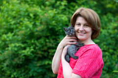 Woman hugging a blue kitten Scottish strait in outdoors Royalty Free Stock Photography