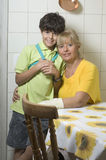 Woman Hugging Boy In Kitchen - Vertical Stock Photo