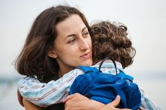 A woman is hugging a boy. Stock Image