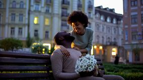 Woman hugging boyfriend, looking with love, holding flowers, romantic date stock images