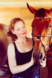 Woman hugging brown horse in stable Stock Images
