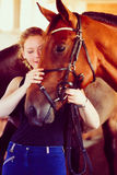 Woman hugging brown horse in stable Stock Photography