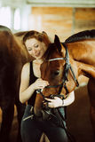 Woman hugging brown horse in stable Royalty Free Stock Photos