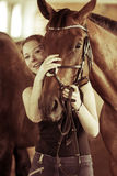 Woman hugging brown horse in stable Royalty Free Stock Image