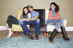 Woman BY Hugging Couple On Sofa Royalty Free Stock Photo