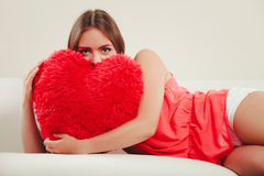 Woman hugging heart shape pillow. Valentines day. Stock Photos