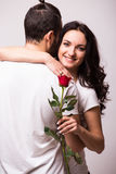 Woman hugging her boyfriend and holding the rose Stock Photos