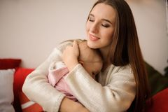 Woman hugging her cute little daughter on hands royalty free stock photography