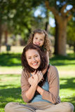Woman hugging her daughter in the park Stock Images