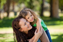 Woman hugging her daughter in the park Royalty Free Stock Photos