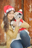 Woman hugging her dog  dressed with red christmas hats Royalty Free Stock Photos