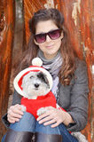 Woman hugging her dog  dressed with red christmas hats Stock Photo