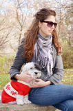 Woman hugging her dog  dressed with red christmas hats Royalty Free Stock Photo
